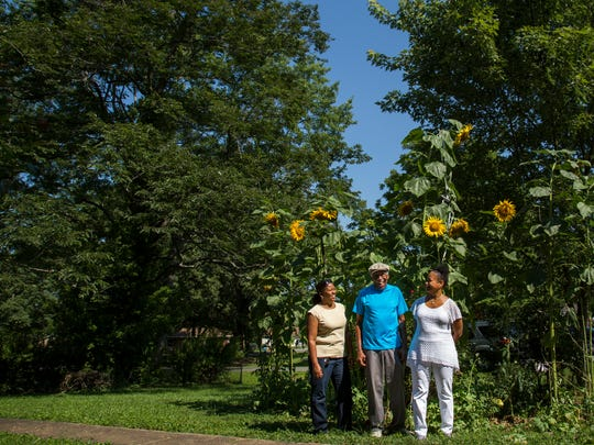 Marvin Porter poses for a portrait in front of his sunflowers with his daughters Carolyn Dyson, left, and Juanita Porter, right.