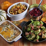 Thanksgiving potluck spread (clockwise from upper right): orange cranberry sauce, brussels sprouts with pancetta; butternut squash gratin; and cornbread stuffing with dried fruit.