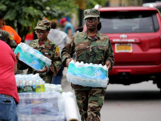 Cases of water are collected Saturday at Rochester's benefit concert for Puerto Rico and other Caribbean islands that were devastated by recent hurricanes.