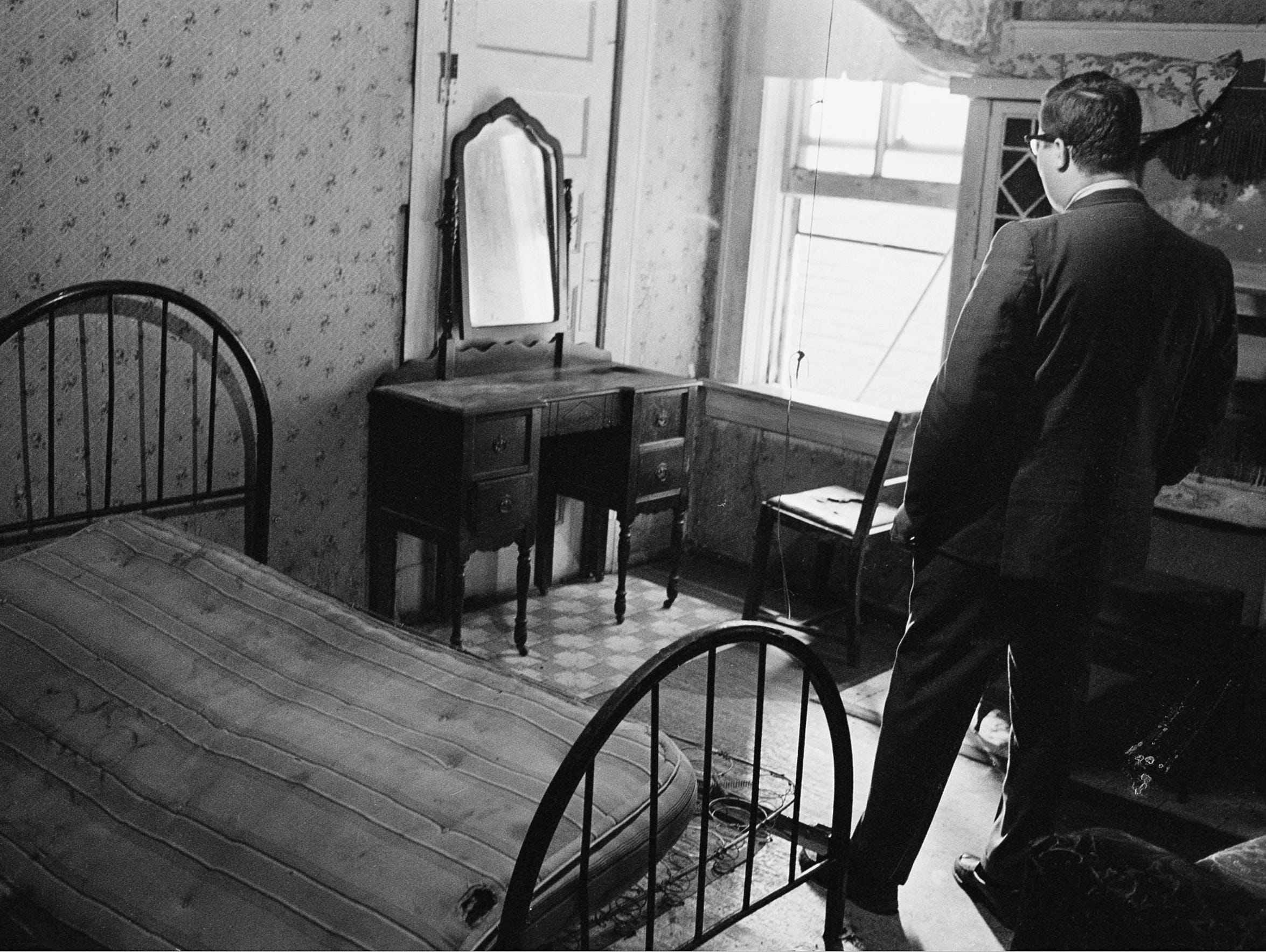 A news reporter stands in the room rented by the assassin