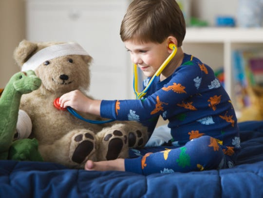 Boy listening to teddy bear's heartbeat with stethoscope