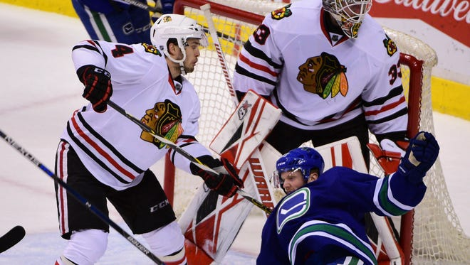 Vancouver Canucks forward Henrik Sedin (33) goes down after a slash by Chicago Blackhawks defenseman Niklas Hjalmarsson (4) during the second period at Rogers Arena.
