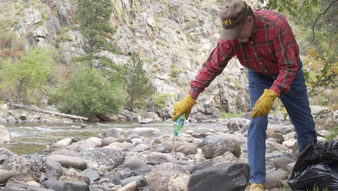 Rod Patrick of Fort Collins, a member of the Rocky Mountain Flycasters a chapter of Colorado Trout Unlimited, empties out a bottle he cleared from the river during their cleanup of the Poudre River, Sept. 24, 2005.