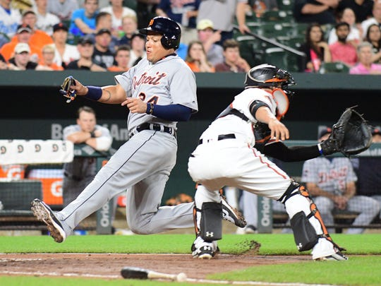Tigers first baseman Miguel Cabrera (24) slides to score a run ahead of the tag by Orioles catcher Welington Castillo (29) in the third inning on Thursday, August 3, 2017, in Baltimore.