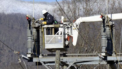 A Duke Energy worker tries to restore power in this 2013 file photo.