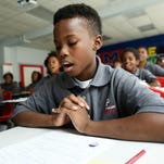 In this 2015 photo, fifth-grader Dareion Clark-Flanagan and his classmates chant in unison during class at ReImagine Prep, one of Mississippi's first charter schools, in Jackson, Miss.