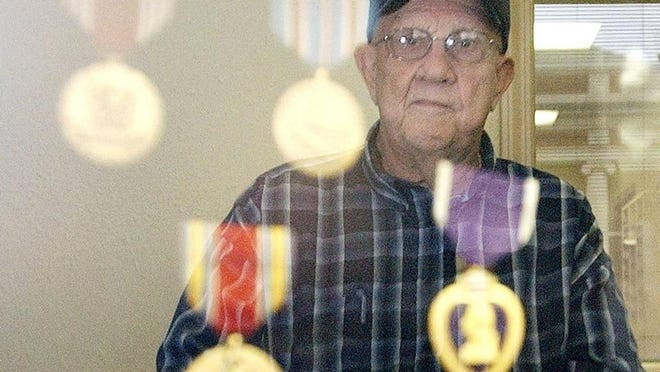Homer Cole is reflected off of a glass case containing medals he was awarded during World War II. -- FILE PHOTO