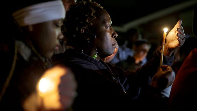 People take part in a candlelight vigil in Ferguson, Mo.