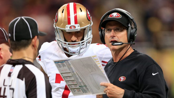 San Francisco 49ers coach Jim Harbaugh, right, and quarterback Colin Kaepernick talk on the sideline Oct. 13, 2014, in St Louis.