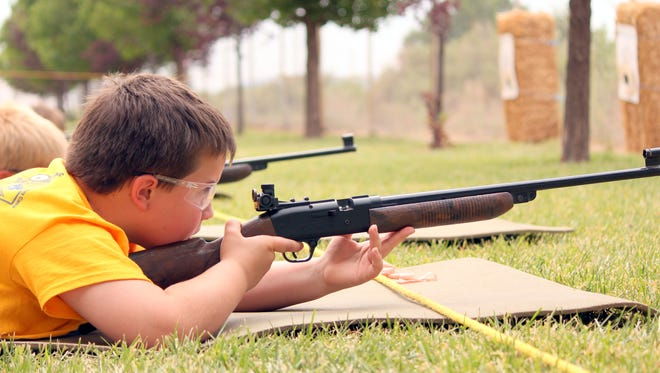 Preston McCarty, 8, takes aim down the rifle range before firing a BB gun Thursday during the Cub Scout Investigators Camp on Thursday. The camp featured various activities for the youth including crafts, storytelling and knot -tying classes.