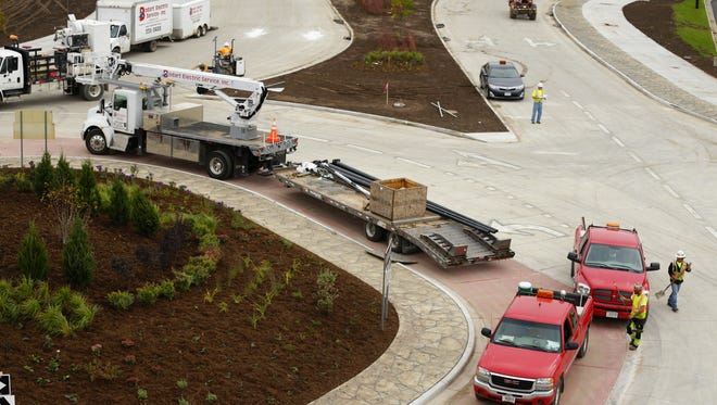 Crews work to complete construction of a roundabout on Velp Avenue before the road's scheduled reopening on Sunday.