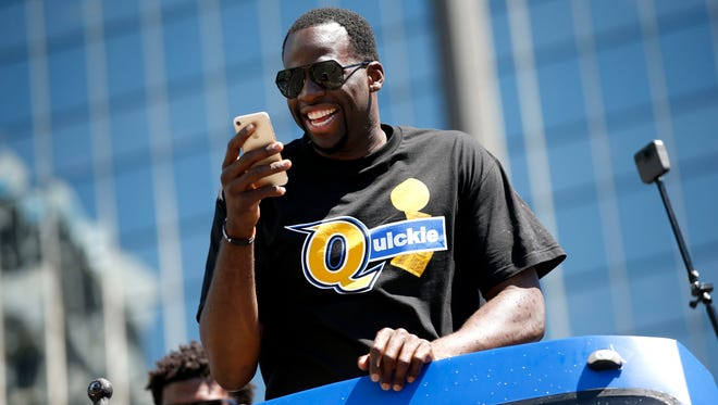 Golden State Warriors forward Draymond Green looks at his phone during the Warriors 2017 championship parade.