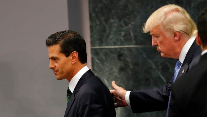 In this Aug. 31, 2016, file photo, Republican presidential nominee Donald Trump walks with Mexico's President Enrique Pena Nieto at the end of their joint statement at Los Pinos, the presidential official residence, in Mexico City.
