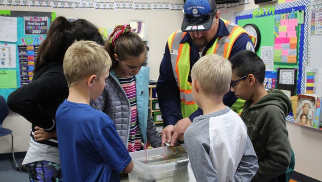 Stephan Klingelmeier brings kids forward to show how pipes rust in a plastic tub during Career Day at Hillrise Elementary School.
