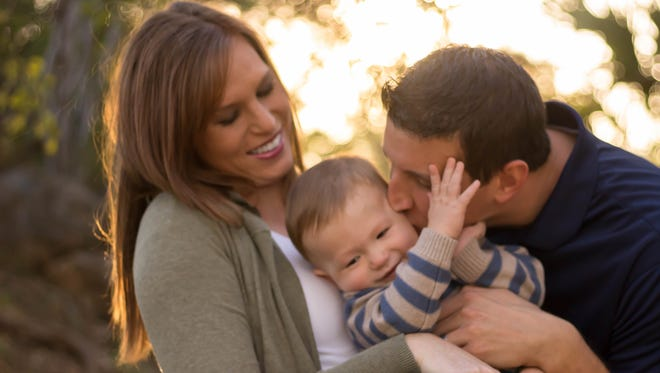 Kally, 16-month-old son Tanner and Matthew Ricci pose for a picture near San Angelo's International Waterlily Collection. The Riccis plan to adopt a baby due in May from a Nevada woman who had an unplanned pregnancy.