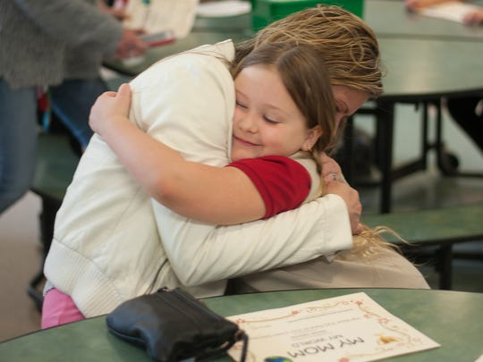 Cecilia Decastro hugs her mother, Janie Nieves, during a Mother's Day celebration at Johnstone Elementary School on Friday.