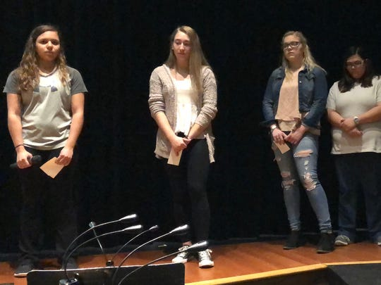From left to right: Juniors Alyssa Blair, Mackenzie Layton, Kiersten Siko, Aria Jewel Barnett and Kali Rotharmel hold a moment of silence for the victims in the Florida school shooting during a Walkup event the morning of Wednesday, March 14 in the auditorium. The students choose to organize the Walkup as an alternative to participating in the National School Walkout.