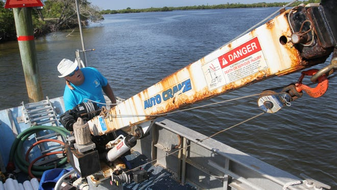 Lee County Natural Resource Technician Brad Martin lifts the crane on a vessel to clear space on the deck while adding temporary channel markers in Jug Creek on Thursday.