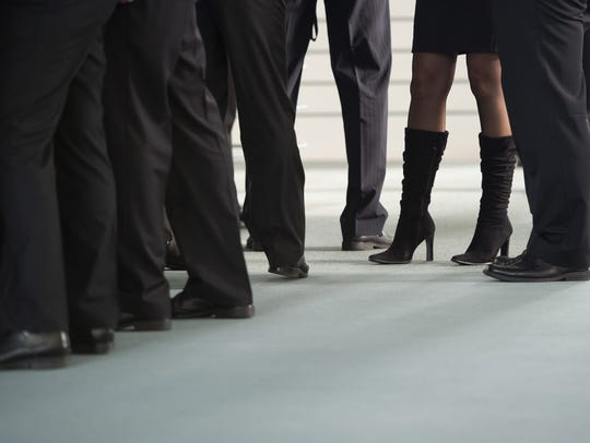 A woman stands surrounded by men at the chancellery