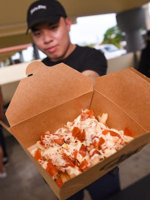 Stax Sliders crew member Felix Mendoza displays an order of pizza fries at Chamorro Village on June 28, 2017.