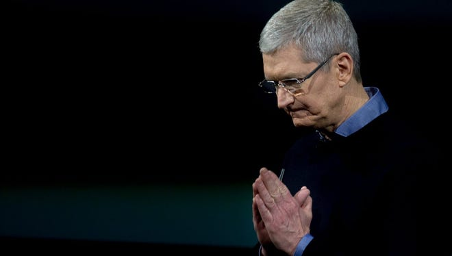 Apple CEO Tim Cook gestures during a media event at Apple headquarters in Cupertino, California on March 21, 2016.