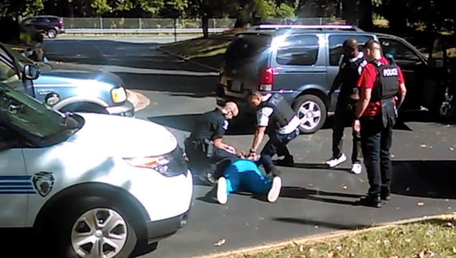 In this image taken from video recorded by Keith Lamont Scott's wife, Rakeyia, on Sept. 20, 2016, Charlotte police squat next to Scott as he lies face-down on the ground after being fatally shot.