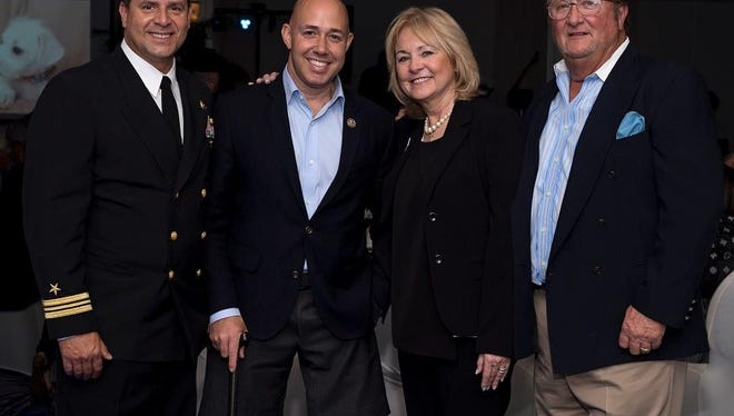 """Master of Ceremonies Hector Delgado (from left), U.S. Rep.  Brian Mast, Furry Friends President Pat Deshong and Bob Deshong enjoy the """"""""For the Love of Animals and their Hero Friends"""" event at Admirals Cove's Harbourview Dining Room on Feb. 10."""