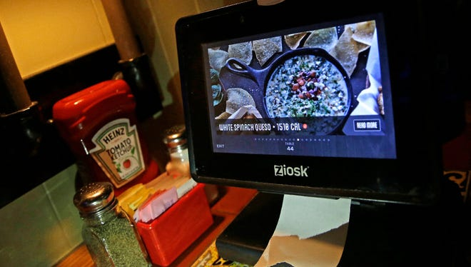 A Ziosk tablet displays an appetizer a customer can order this month at a Chili's restaurant  in Andover, Mass. Restaurant chains are making it easier to order food with a few taps of the screen, so much so that you may lose sight of how much you're spending.