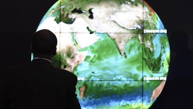 Alain Jocard, AFP/Getty Images A participant looks at a projection of the Earth on the opening day of the COP 21 United Nations climate summit. A conference attendee looks at a projection of Earth on the opening day of the COP 21 United Nations conference on climate change on Nov. 30, 2015, in Le Bourget, on the outskirts of Paris.