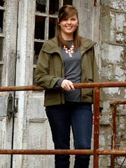 Marianne Barnes, 28, poses in front of the Old Taylor Distillery in Woodford. Barnes is the first female Master Distiller since prohibition times. The Old Taylor Distillery has been shuttered since the 1972. Barnes and her two business partners purchased it last year with the hopes of refurbishing it and producing spirits by the end of the year. County April 11, 2015
