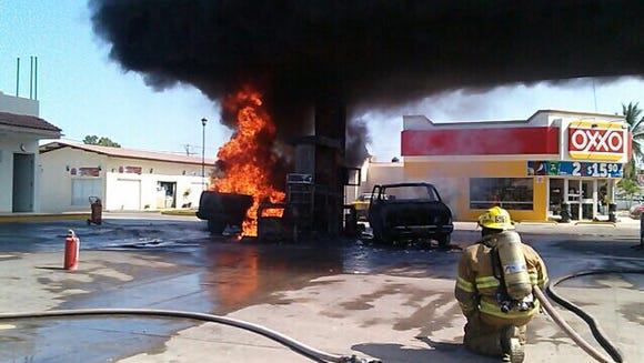 Firefighters work to put out a fire in a petrol station