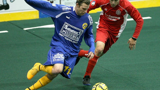 """Alex Megson of the Rochester Lancers protects the ball from Ontario's Joey Pacheco in Rochester's home opener in November. The Lancers and their opponents have complained about the turf for the gaps between its sections (upper center) and the """"ski jump"""" effect on its advertising patches."""