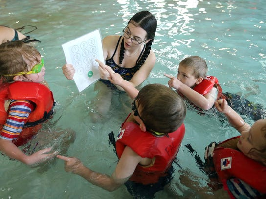 Liana Ivan teaches kids how to dial 911 during a swim lesson at Fairmont Aquatic Center in Salt Lake City on Tuesday, May 22, 2018.