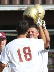 Arlington baseball teammates celebrate during their win over Scarsdale in a Section 1 Class AA semifinal on May 24.
