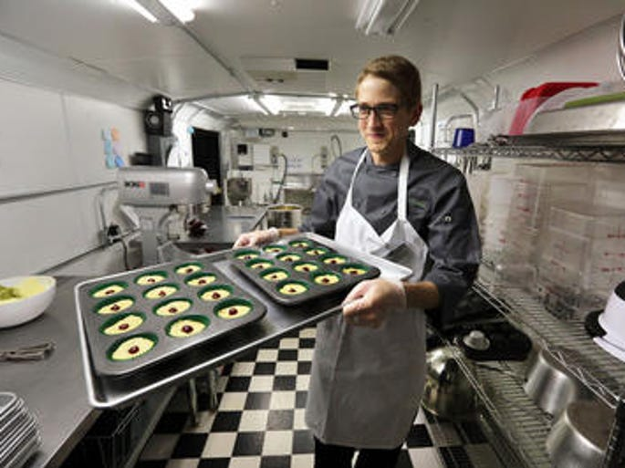 Chef Alex Tretter carries a tray of cannabis-infused peanut butter and jelly cups to the oven for baking, at Sweet Grass Kitchen, a well-established gourmet marijuana edibles bakery which sells its confections to retail outlets, in Denver.