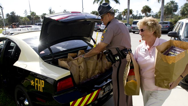 """A Florida Highway Patrol trooper helps at the 2014 inaugural """"Stuff the Charger"""" event.   ."""