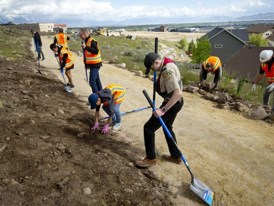 Ethan Blood, 15, packs down soil as he and volunteers help complete his Eagle Scout Service Project to create a walkable path connecting nearby neighborhoods to Ignite Entrepreneurship Academy and a future park just northwest of the charter school in Lehi, Utah.