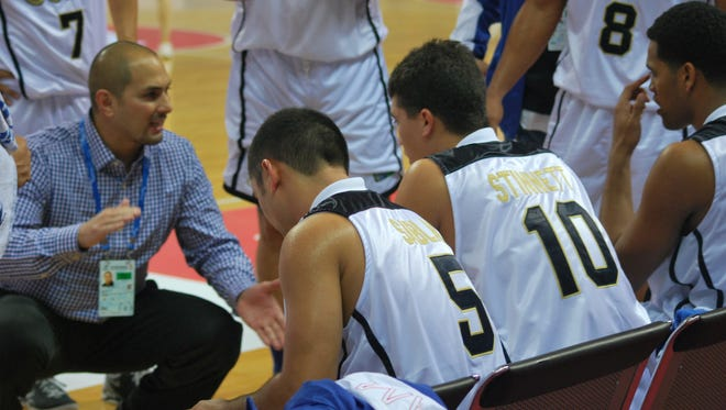 In this photo taken in October 2013 from the East Asian Games in Tianjin, China, Team Guam men's basketball coach E.J. Calvo talks to his team late in a game against Mongolia. Calvo said he hopes to have 10 or more players from the basketball academy playing college ball in the next four years, as a feeder system to the men's national team.