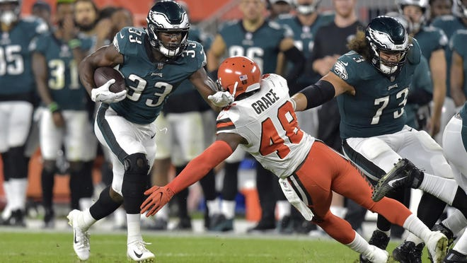 Philadelphia Eagles running back Josh Adams carries as Browns linebacker Jermaine Grace reaches for him during a preseason game in 2018.