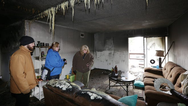 David Dashkovitc, Casey Miller and Catre Miller assess the damage after a fire destroyed their apartment at 750 Maple St.
