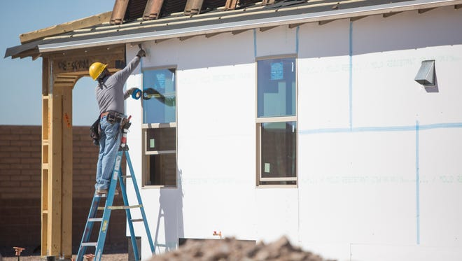Alberto Vargas of Osborn Construction works on a home in one of the Vistancia communities northwest of Loop 101, where many of Peoria's new homes are being built. The city was one of only four in Maricopa County to see residential permits increase.