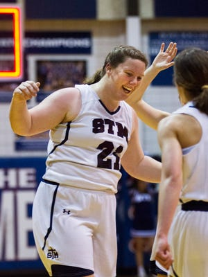 St. Thomas More's Bailey Hemphill celebrates her buzzer-beater with teammates during the Lady Cougars' 4A regional win Monday.