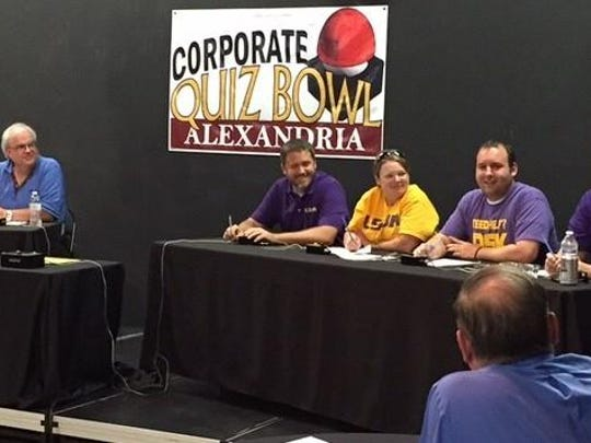 Teams from The Town Talk (left) and LSUA (right, seated) listen Tuesday to quizmaster Tom Harmeyer (right, standing) during a semifinal match of the Corporate Quiz Bowl Alexandria.