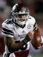 Mississippi State's Dak Prescott (15) keep the ball and runs during the the first half against Arkansas, Saturday, Nov. 21, 2015 in Fayetteville, Ark.
