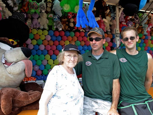 Margaret Frehler of Appleton, her son Daniel Miller and her grandson Stephen Miller pose by a game booth Friday August 29, 2014 in Plymouth.  The three generations have been involved in the carnival business for years.