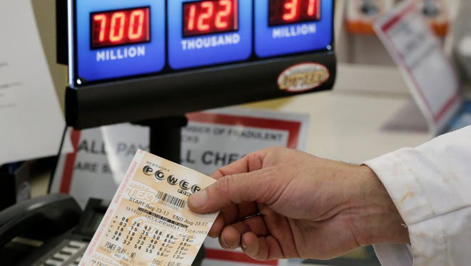 A customer is handed a Powerball ticket in Omaha, Neb., Wednesday, Aug. 23, 2017.