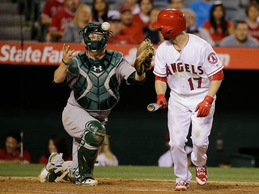 Oakland Athletics catcher Stephen Vogt reaches for the ball as Los Angeles Angels' Shane Robinson (17) walks during the fourth inning of a baseball game Saturday, June 25, 2016, in Anaheim, Calif. (AP Photo/Gregory Bull)