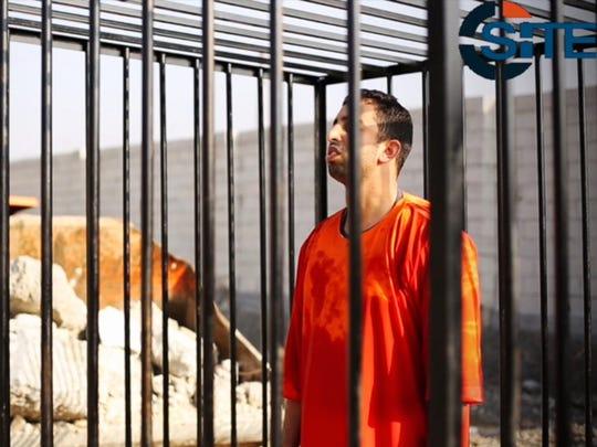 Jordanian pilot Lt. Muath al-Kaseabeh stands in a cage