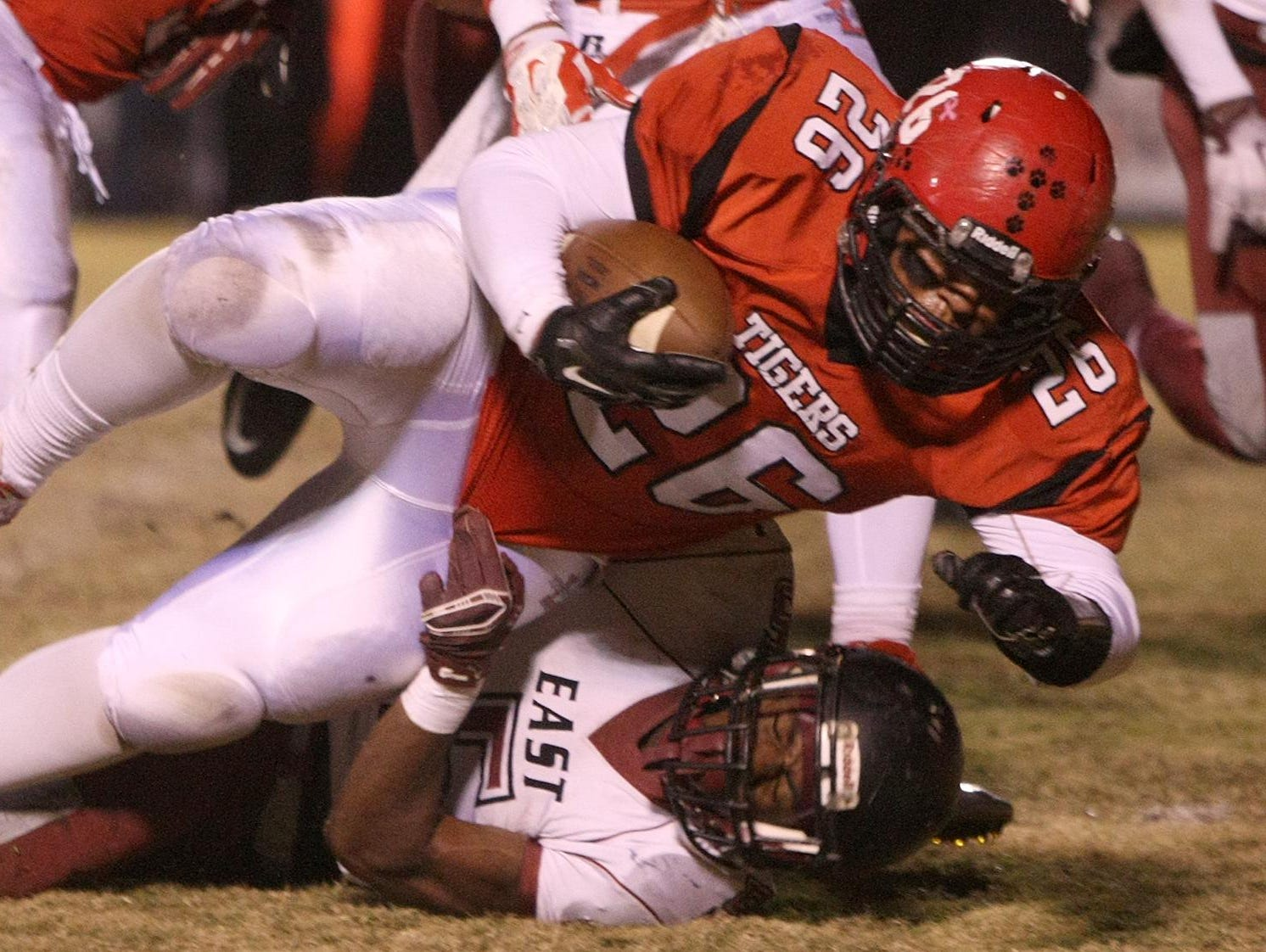 Lexington's Kendal Bevelot (26) is tackled by Memphis East's Devante Turner (5) at Tiger Stadium on Friday.