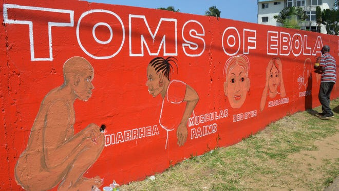 Liberian street artist Stephen Doe paints a mural designed to inform people about the symptoms of the deadly Ebola virus in Monrovia, on Sept. 8, 2014.